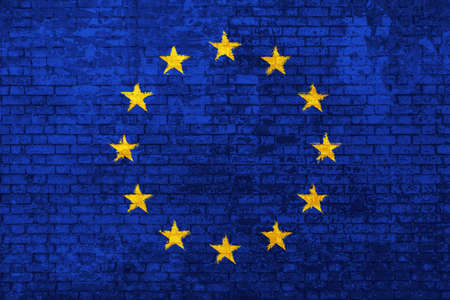wall of bricks painted with the flag of Europe, blue with yellow stars. 3d background. Concept of social barriers of immigration, divisions, and political conflicts in Europe.