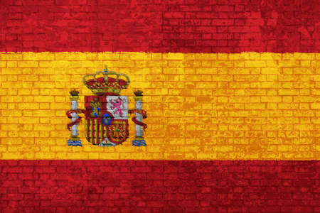 Wall of bricks painted with the flag of Spain, red and yellow colors. 3d background. Concept of social barriers of immigration, divisions, and political conflicts in Spain.
