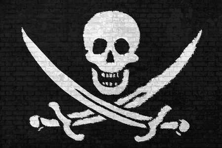 wall of bricks painted with the Pirate Flag of Calico Jack Rackham, white skull and swords crossing on black wall background. Concept of social barriers and divisions or political conflicts.