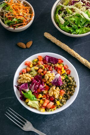 Healthy autumn salad bowl with nuts, green lentils, tomato corn, lettuce, spinach with sesame seeds
