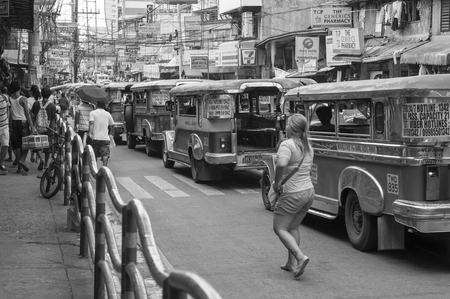 Woman walking by Jeepneys in Novaliches, Quezon City, Philippines on the 19 June 2016 Editorial