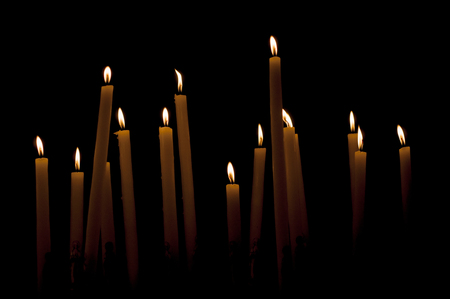 Close-up of a burning candles in a low-key image