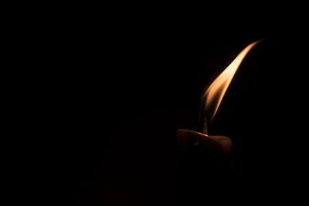 Close-up of a burning candle in a low-key image