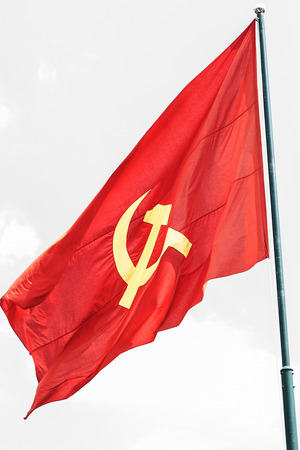 Large communist flag floating in the wind with a blue sky background Stock Photo