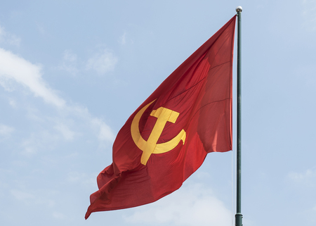 Large communist flag floating in the wind with a blue sky background 写真素材