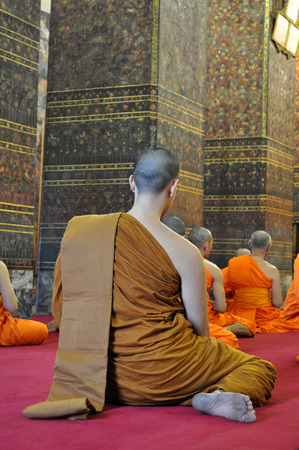 A novice and some monks are praying in Wat Pho, Bangkok