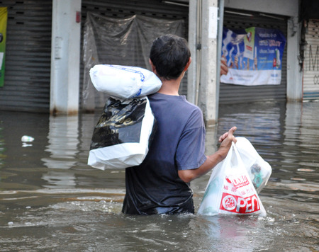 A man is carrying possessions back in a flooded street of Bangkok, Thailand, on the 06 November 2011