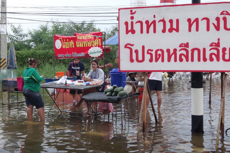 Life and business are as usual in flooded Pathum Thani, Thailand, in October 2011.