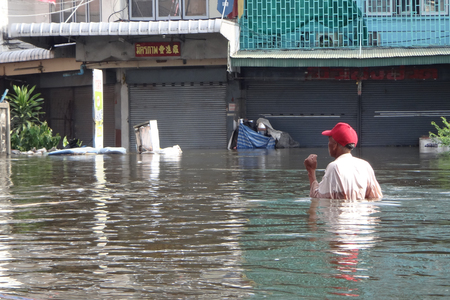 People are coping with the water in a flooded street in Rangsit, Thailand, in October 2011. Editorial