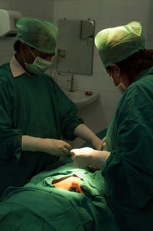 Surgeons and nurses conduct a tubal ligation on a young woman in Bihar, India. Editorial