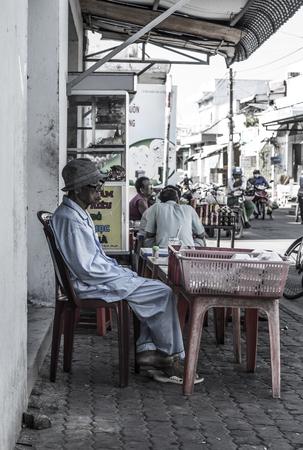 Old Vietnamese man in pyjamas is sitting in a street in Can Gio, Vietnam.