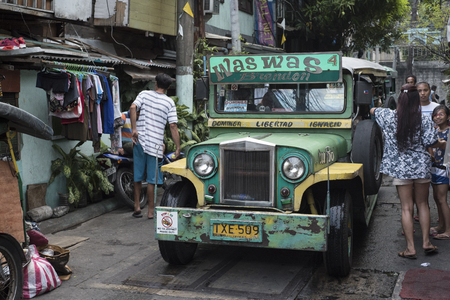 People and a stopped jeepney  in a small street of Manila, the Philippines. Stock Photo - 112496451