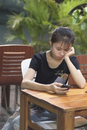 Vietnamese woman is browsing on her mobile on a restaurant terrace in Ho Chi Minh City, Vietnam.