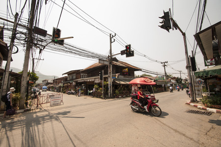 A mobile Walls ice  creams seller passes a quiet crossing on her motorbike in Pai, Thailand.