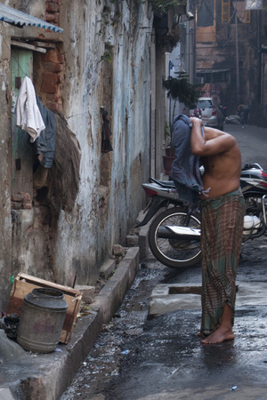 Indian man showers in a street of Kolkata, India.