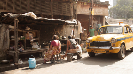 People sit together on a bench next to a taxi in a street of Kolkata, India.