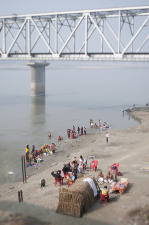 People meet by a bridge on the Ganges river in Bihar, India.
