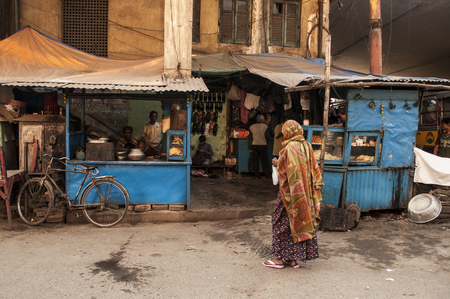 Indian woman stands by streets shops in Kolkata, India.