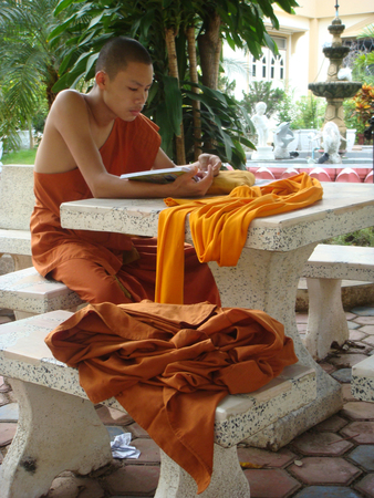 Thai Buddhist novice studying in a temple's outdoors. Standard-Bild - 112496694