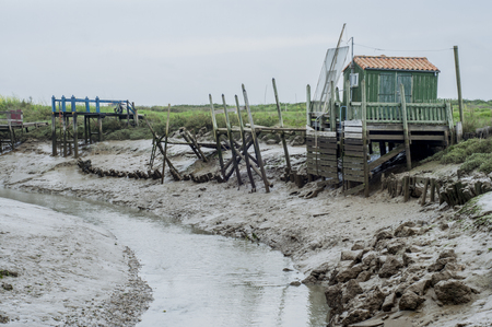 Wooden hut by a muddy river stream on the French Atlantic coast.