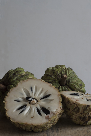 Full and half-cut custard apples on a wooden board and grey background Stock Photo