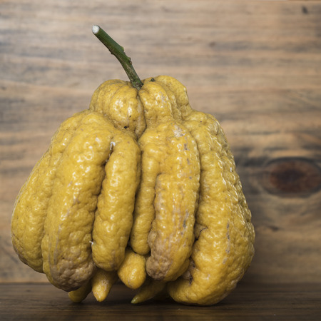 Buddhas hand citrus fruit on a wooden board and background. 写真素材