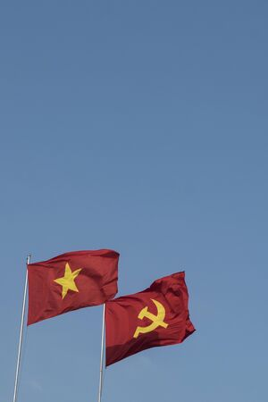 Vietnamese and communist flags in the wind on a blue sky