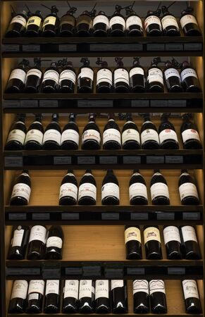 Very expensive French wines displayed in wooden wall with price tags in Vietnamese Dong