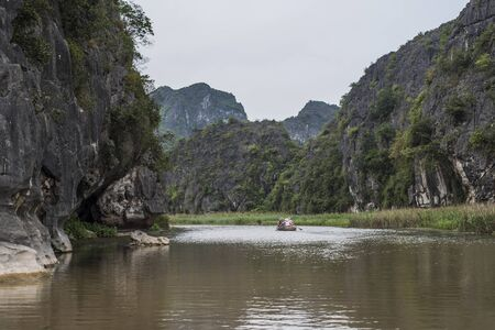 Ninh Bins, Viet Nam, scenery of river and hills with a couple of tourists on a rowing bamboo raft