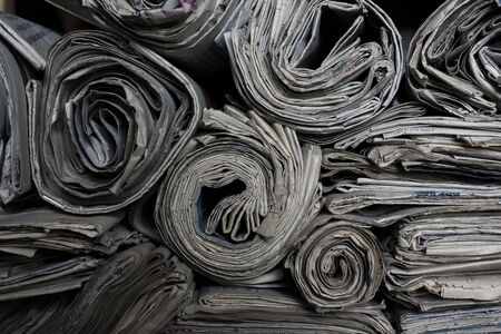 Rolled newspapers on top of each others, seen from the side Imagens
