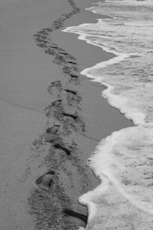 Waves follow the track of human footprints on a beach's sand Imagens