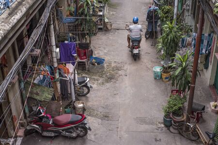 Vietnamese man rides his vintage moped in the old alley of Hao Si Phuong in Ho Chi Minh City
