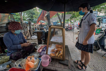 Vietnamese woman makes and sells snacks to a student in a street of Ho Chi Minh City