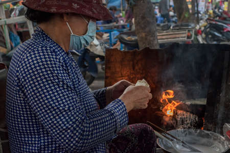 Vietnamese woman makes and sells snacks in a street of Ho Chi Minh City