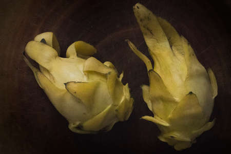 Top view of two yellow dragon fruits on a wooden board