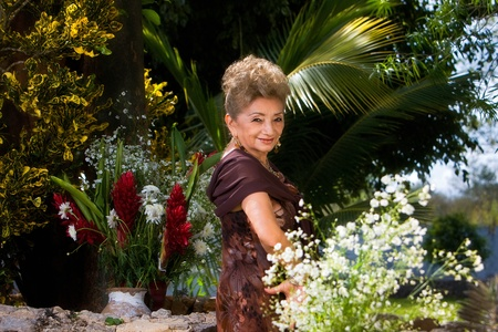 Elegant Latin woman in her garden Stock Photo