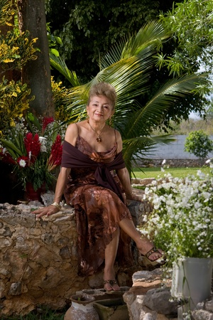 Old elegant Lady in a garden of flowers and palms