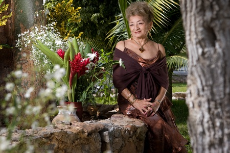 Elegant older Lady looks at colorful flowers