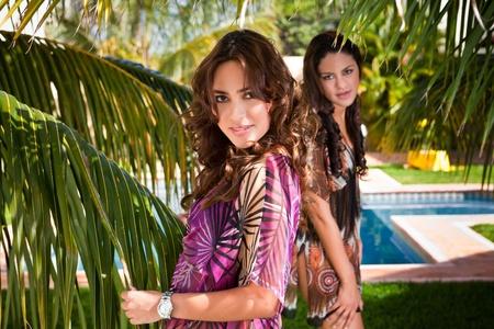 2 Latin girls under palm trees Stock Photo