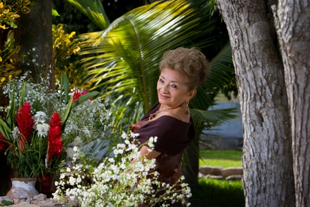 Old Latin Lady dances in a garden Stock Photo
