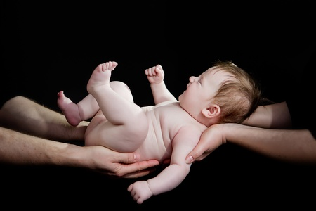naked child: A baby in the hands of her proud parents Stock Photo