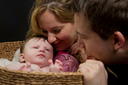 A baby in a basket watched by her parents