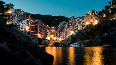 one of the five lands cities riomaggiore photographed from a low angle on the water as a long exposure at night