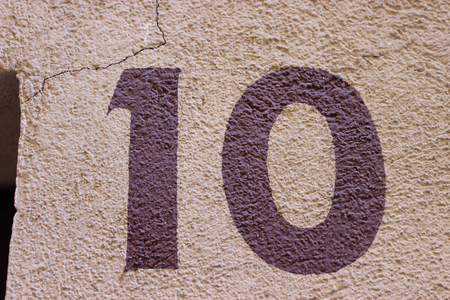 burgundy background: Number 10 painted on the wall of a house in France