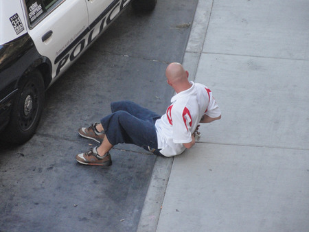 enforcing: Las Vegas, USA - August 8 2010:  Man arrested by Las Vegas police. Caucasian Man In Handcuffs Sitting On The Sidewalk, Las Vegas strip