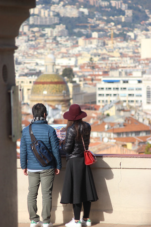 nice butt: Nice, France - November 30 2015: Back View of Young asian Couple in Love in front of an Aerial View of the City of Nice, France Editorial