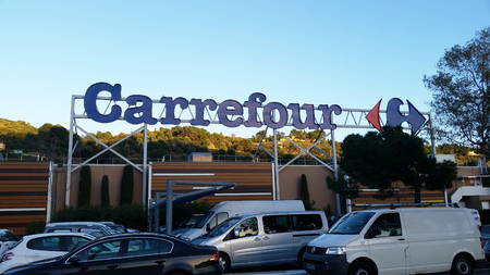 carrefour: Nice, France - February 13 2016: Sign and Logo above a Carrefour Supermarket in Nice Lingostiere. Carrefour is one of the Largest Supermarket Chain in the World Editorial
