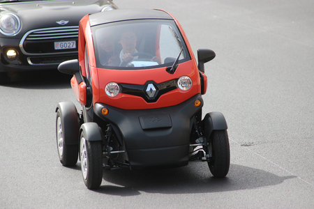 electric avenue: Monte-Carlo, Monaco - April 6, 2016: Red Electric Car Renault Twizy on Avenue dOstende in Monaco. Old Woman Driving an Electric Car Renault Twizy in the south of France