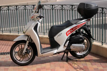 a white police motorcycle: Monte-Carlo, Monaco - April 6, 2016: Honda SH 125i Motorbike Standing in Front of the Police Station. Motorcycles of Monaco Police Patrol on the City Street of Monte-Carlo Editorial