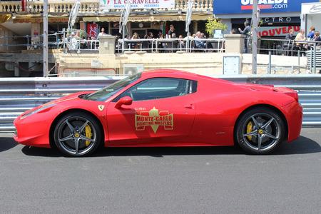 italia: Monte-Carlo, Monaco - April 28, 2016: Red Ferrari 458 Italia Parked on the Street in Monaco. Guardrail of the Monaco Grand Prix in the Background